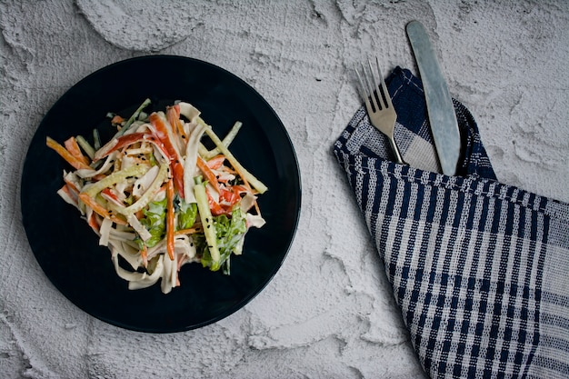 Nourriture diététique, salade de légumes frais avec une imitation de bâtonnet de crabe, assaisonnée de sauce soja et sésame japonais