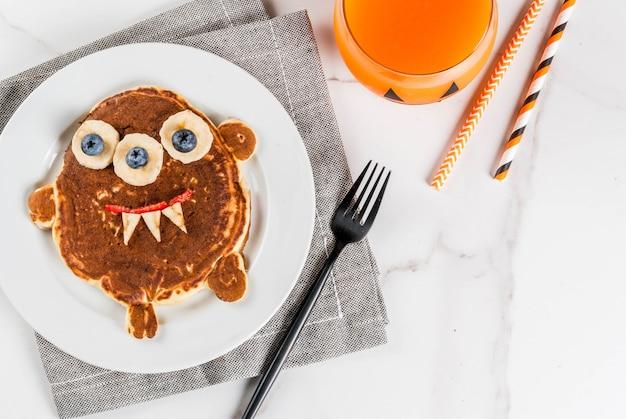Nourriture drôle pour halloween. crêpe de petit-déjeuner pour enfants décorée comme un monstre effrayant, avec banane, baies, avec jus de smoothie à la citrouille, tableau blanc