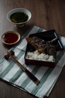 Nourriture du japon, saba grillé ou maquereau avec sauce sucrée servi avec soupe miso et riz cuit placé sur table en bois