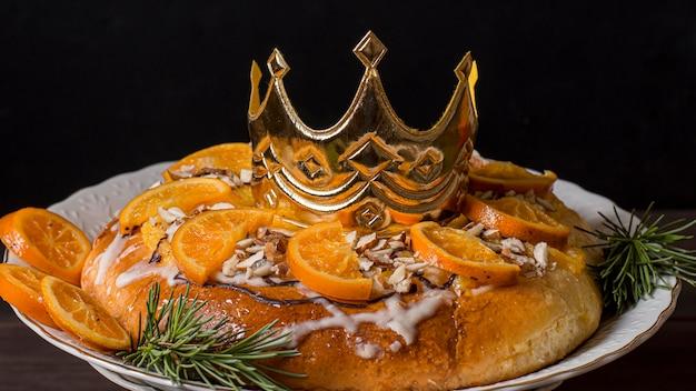 Nourriture du jour de l'épiphanie avec des oranges tranchées et une couronne dorée
