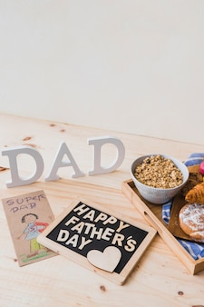 Nourriture du petit déjeuner et salutation près de dessin et papa écriture