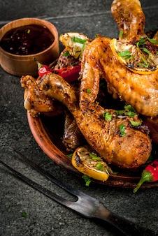 La nourriture d'été. idées pour barbecue, grillades. cuisses de poulet, ailes grillées, frites au feu. avec piment fort, citron et sauce barbecue. table en pierre sombre, sur plaque noire espace copie