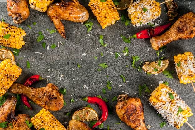 La nourriture d'été. idées pour barbecue, grillades. maïs et poulet (cuisses, ailes) grillés, frits au feu. avec une pincée de fromage (elotes), piment fort, citron. table en pierre sombre. copier la vue de dessus de l'espace