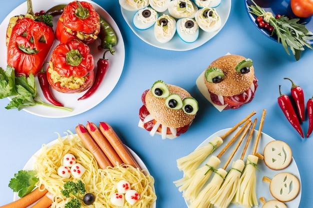 Nourriture de fête d'halloween. poivrons farcis aux visages effrayants, balais de sorcières au fromage, hamburgers monstres