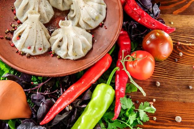 Nourriture géorgienne faite maison appelée khinkali sur plaque brune,