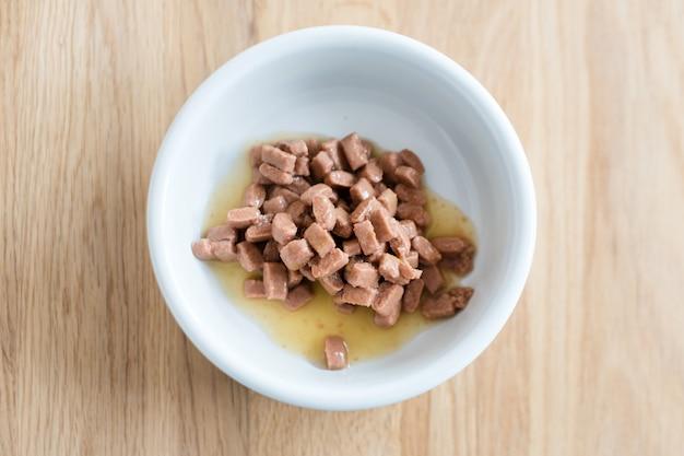 Nourriture humide pour chats et chiens dans un bol blanc sur plancher en bois