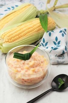 Nourriture indonésienne : bubur jagung mutiara, bouillie traditionnelle indonésienne sur table en bois. fait de maïs, de sagou perlé, de lait de coco et de sucre. populaire en javanais et en aceh