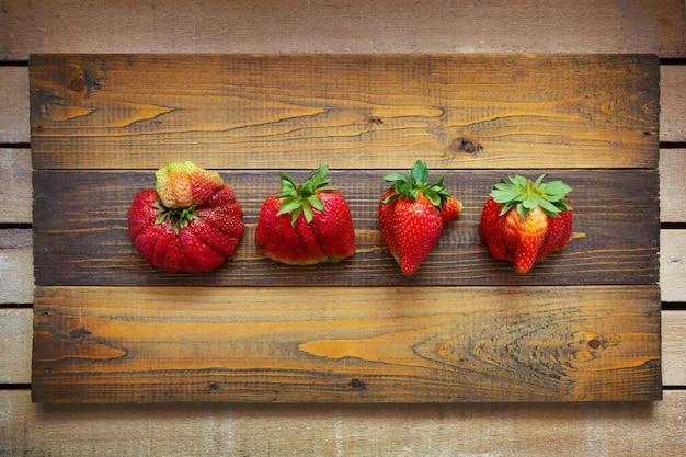 Nourriture laide. fraises étranges déformées sur du bois.