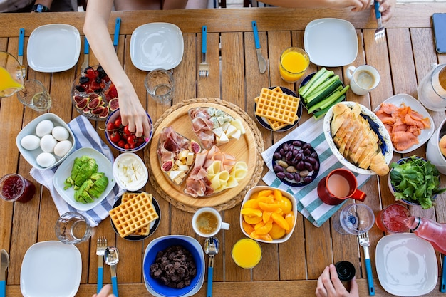 Nourriture et mains des gensles gens prennent le petit déjeuner à la vue de dessus de tablepetit-déjeuner pour la familledîner