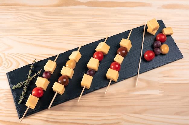 Nourriture à manger avec les doigts. tranches de fromage et tomates sur une brochette. brochettes italiennes avec du fromage