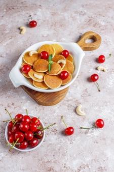 Nourriture à la mode - céréales mini crêpes. tas de crêpes aux céréales avec des baies et des noix.