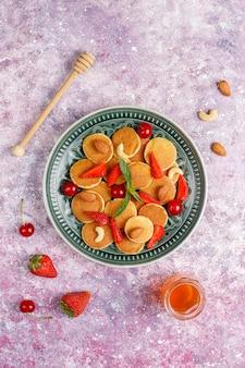 Nourriture à la mode - mini-crêpe aux céréales. tas de crêpes aux céréales avec des baies