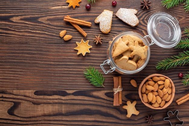 Nourriture de noël - un pot avec des biscuits et un bol d'amandes parmi les ingrédients pour les biscuits de fête