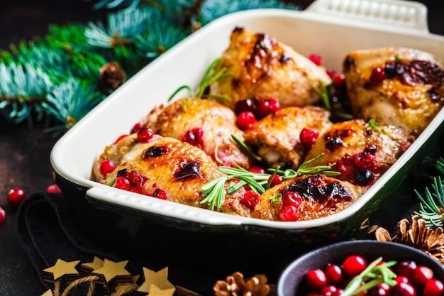 Nourriture de noël, viande de poulet au four avec canneberges et romarin dans le plat du four