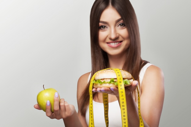 Nourriture nuisible. une jeune fille est aux prises avec des aliments malsains. le choix entre une pomme et un burger.