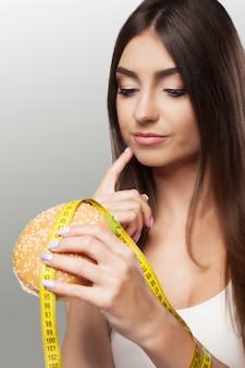 Nourriture nuisible. une jeune fille se débat avec des aliments en surpoids et malicieux. le choix entre pohudannam et burger.