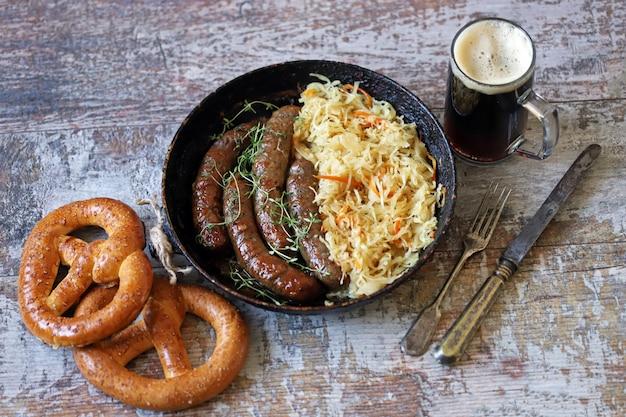 Nourriture d'oktoberfest. saucisses bavaroises chaudes avec choucroute dans une casserole. délicieuse cuisine du festival de la bière