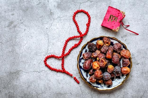 Nourriture populaire pendant l'iftar dattes sèches karan chapelet sur fond de béton