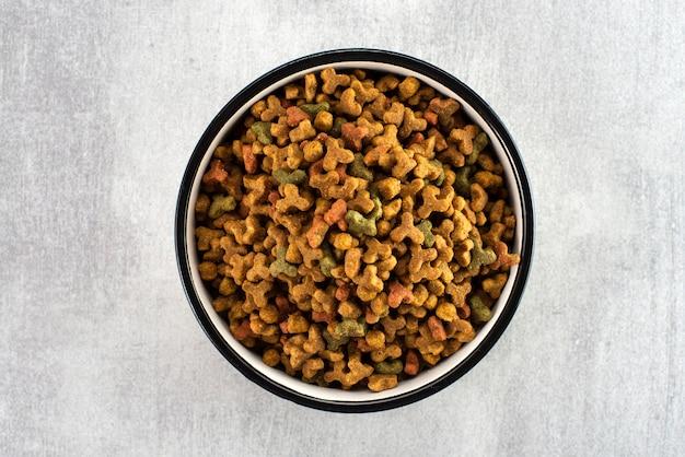 Nourriture pour animaux dans un bol sur une surface grise