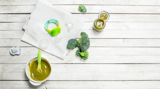Nourriture pour bébé purée de bébé de brocoli sur un fond en bois blanc