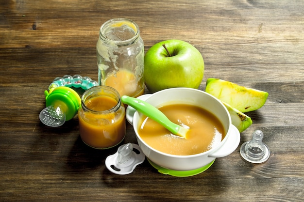 Nourriture pour bébé purée de bébé de pommes vertes sur un fond en bois