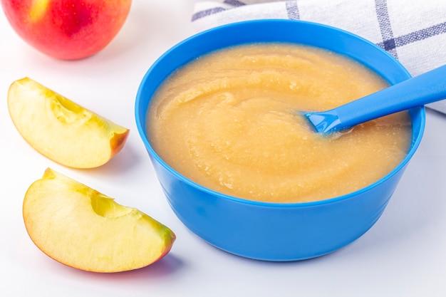 Nourriture pour bébés. compote de pommes maison fraîche. bol bleu avec purée de fruits sur tissu et pommes coupées sur table. le concept d'une bonne nutrition et d'une alimentation saine. texte bio et végétarien