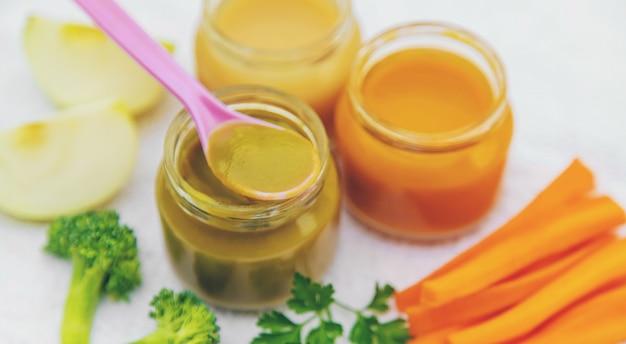 Nourriture pour bébés. purée de légumes et de fruits en pots. mise au point sélective.