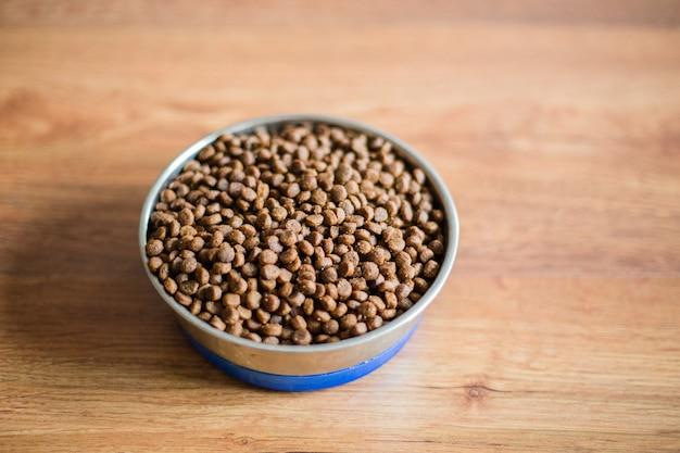 Nourriture pour chat dans un bol sur fond de bois, vue du dessus