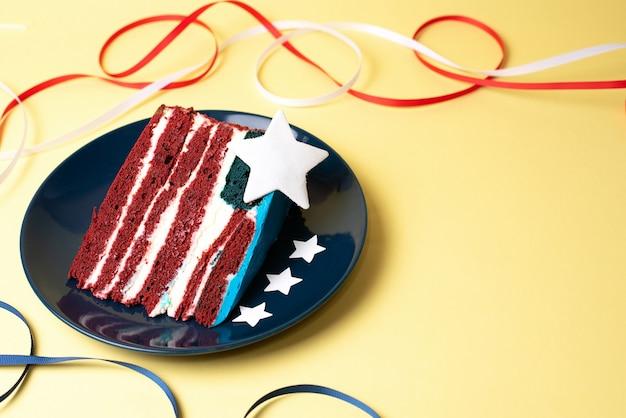 Nourriture pour la fête de l'indépendance, un morceau de gâteau comme le drapeau américain avec des rubans blancs, rouges et bleus et des étoiles sur fond bleu, gros plan.