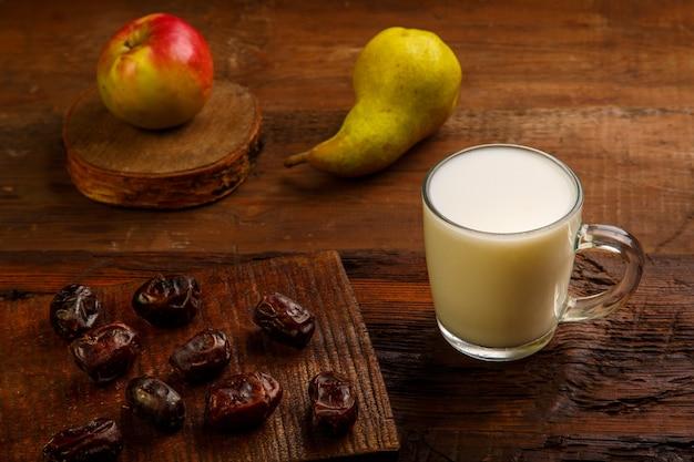Nourriture pour l'iftar dans le saint ramadan sur une table en bois dates, fruits et ayran