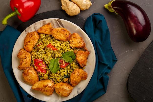 Nourriture pour suhoor en boulgour du ramadan rapide avec du boeuf dans une assiette sur une serviette bleue à côté de légumes. photo horizontale