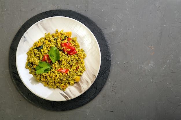 Nourriture pour suhoor dans le ramadan bulgur post avec des légumes dans une assiette sur un fond gris. photo horizontale