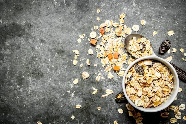 Nourriture de remise en forme. céréales aux fruits secs dans la tasse sur table en pierre.