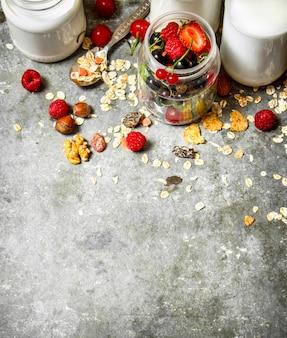 Nourriture de remise en forme. muesli aux baies, noix et lait en bouteilles. sur la table en pierre.