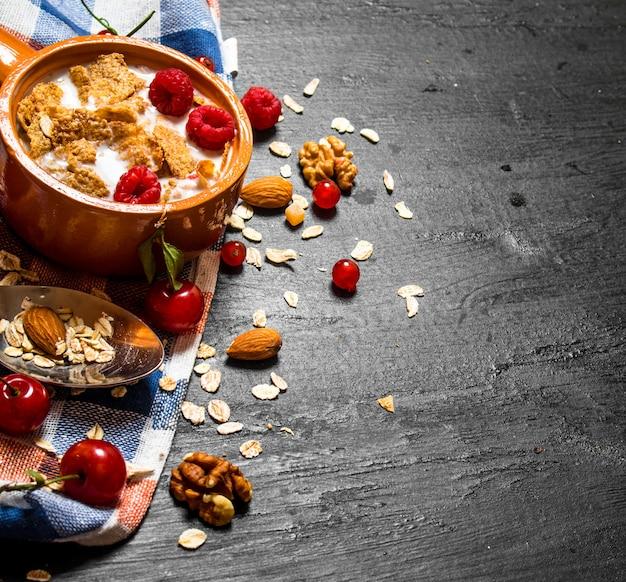 Nourriture de remise en forme. muesli aux baies, noix et lait dans le bol sur une table en bois noire.