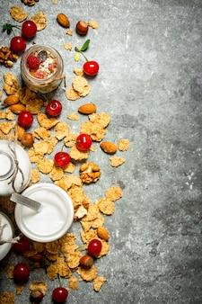 Nourriture de remise en forme. muesli aux baies sauvages et lait en bouteilles sur table en pierre.