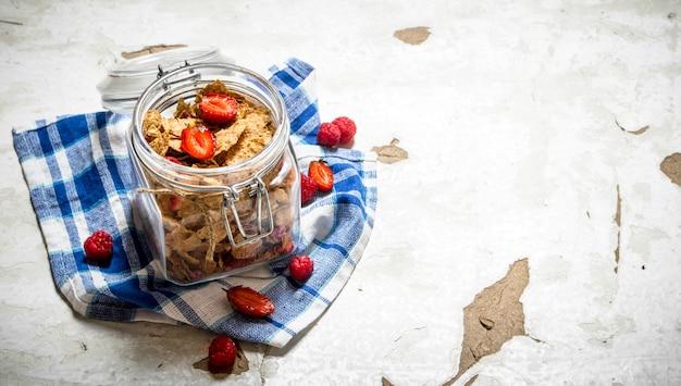 Nourriture de remise en forme. muesli aux fruits rouges dans un pot sur tissu sur table rustique.
