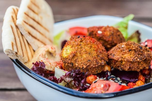 Nourriture de rue israélienne. salade de falafels au houmous, betterave rouge et légumes dans un bol dans un restaurant.