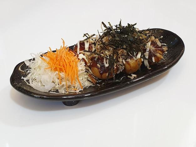 Nourriture de rue japonaise de takoyaki sur le blanc