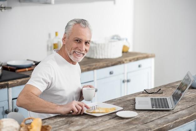 La nourriture saine. bel homme mûr gardant le sourire sur son visage et regardant la caméra tout en mangeant une omelette