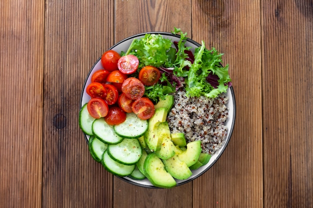Nourriture saine. bol budha avec quinoa, avocat, concombre, salade, tomate, huile d'olive.