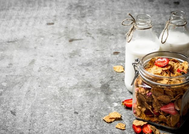 Nourriture saine. céréales aux fraises et lait sur table en pierre.