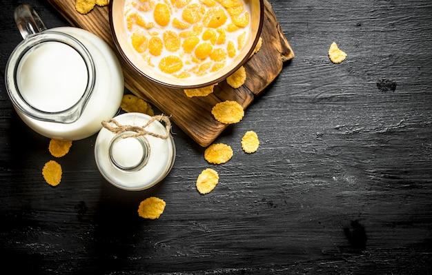 Nourriture saine. cornflakes avec du lait sur planche de bois.