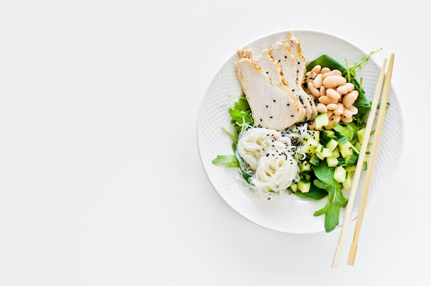 Nourriture saine et équilibrée, bol de nouilles en verre, haricots, poitrine de poulet, épinards, roquette et concombre