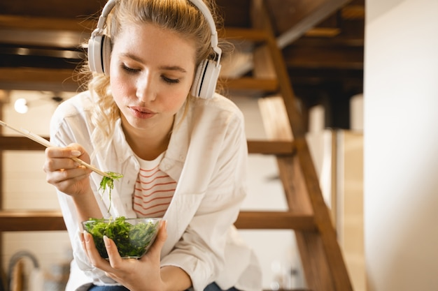 La nourriture saine. fille gaie écoutant de la musique tout en mangeant un plat sain