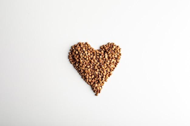 La nourriture saine. forme de coeur à base de grains de sarrasin sur fond blanc. vue de dessus. copie espace