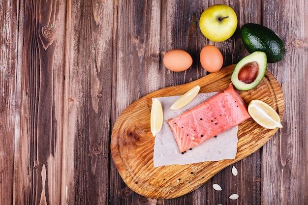 Nourriture saine et fraîche. saumon cru servi avec citrons, œufs, pommes, avocat et couteaux