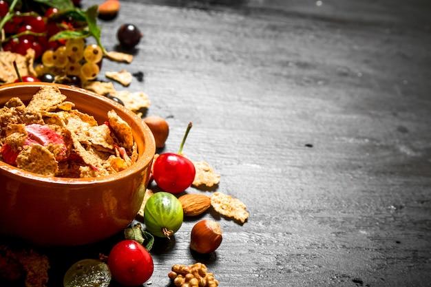 Nourriture saine. muesli aux fruits des bois. sur une table en bois noire.