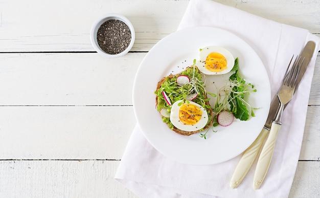 Nourriture saine. petit déjeuner. sandwich aux œufs d'avocat avec du pain de grains entiers sur une table en bois blanc. vue de dessus. mise à plat