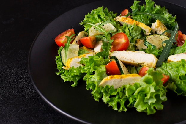 Nourriture saine, salade de poulet, tomates cerises, courgettes, roquette et laitue